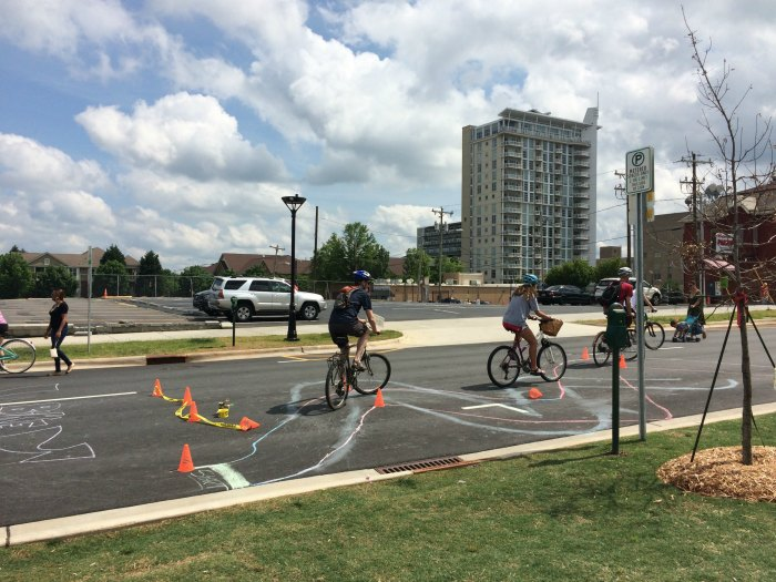 Cyclists riding a mini chalk course at Open Streets 704