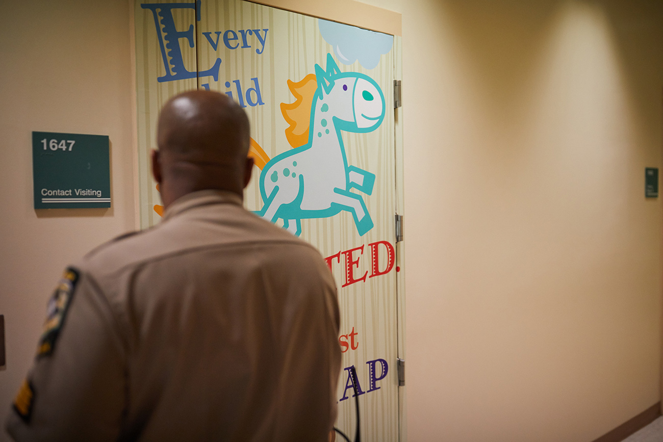 Behind a door with a teddy bear on it, inmates reconnect with their children in the jail's new child-friendly visitation room